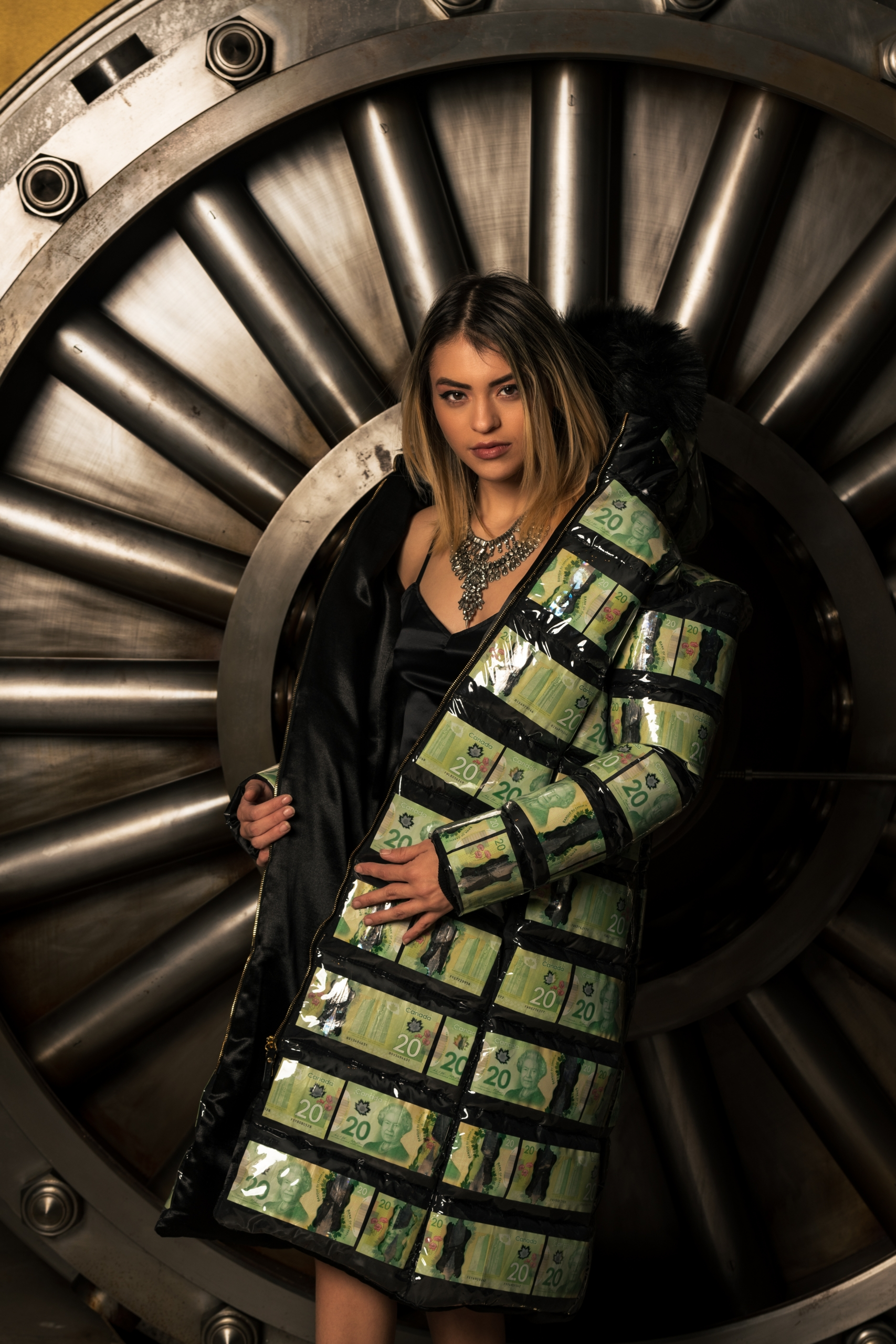Coat made out of 20 canadian bills. model wearing nice necklace in front of a door of a bank vault.